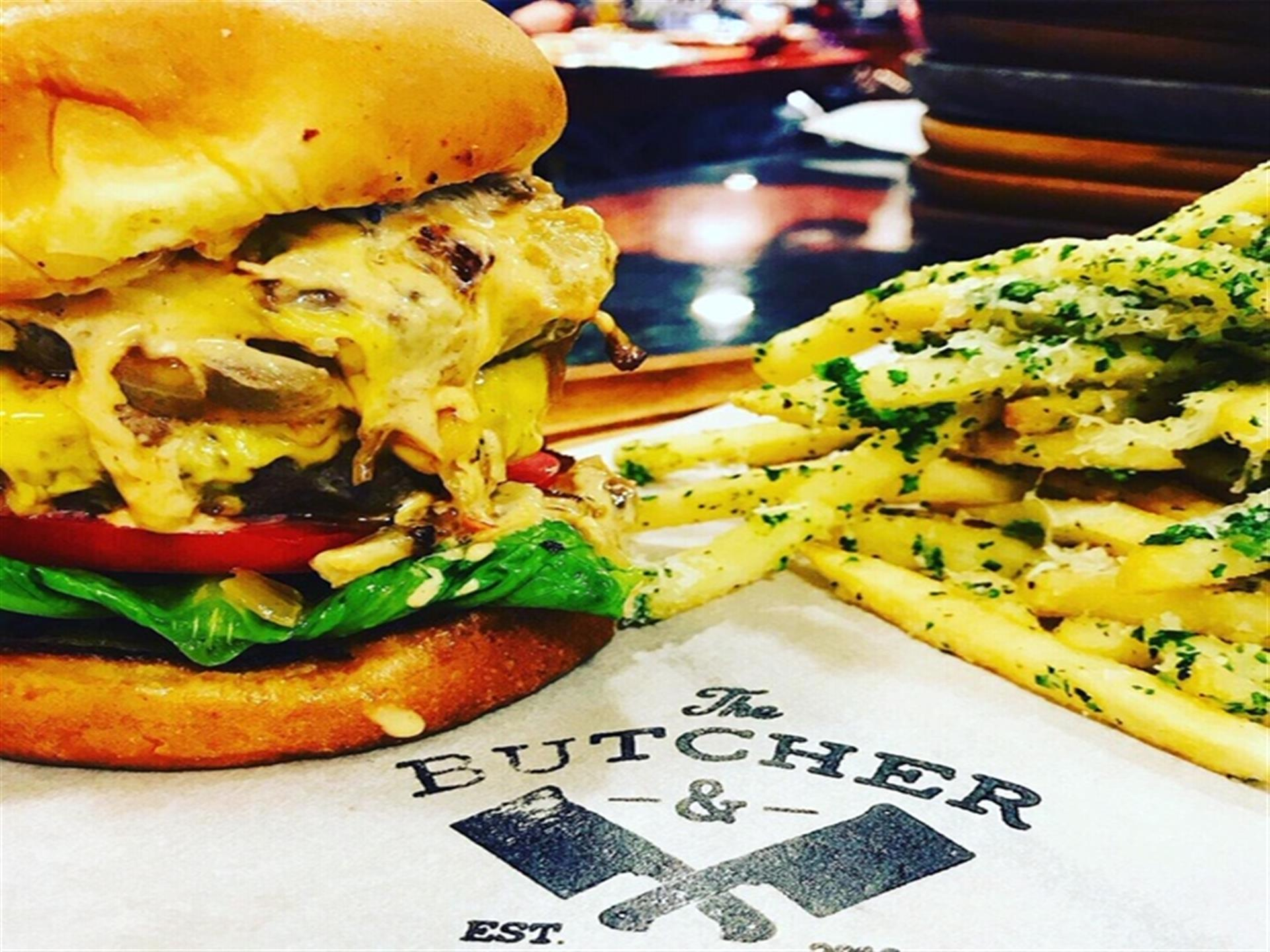 A loaded double cheeseburger with tomato, lettuce and onions, with a side of french fries on a wooden board