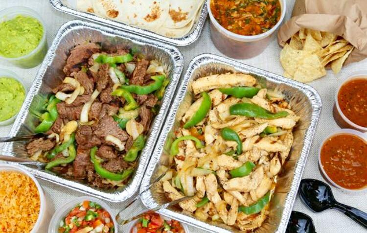 Tin trays of steak and chicken fajitas with tortilla shells, chips and salsa