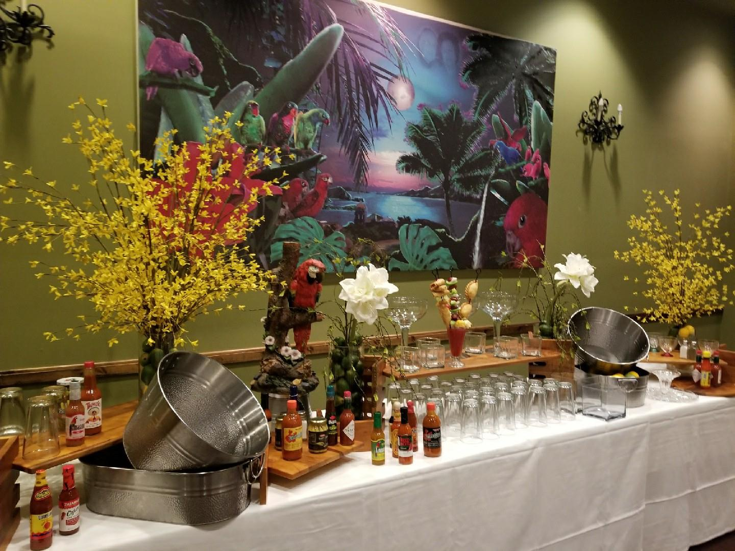 Catering setup on a table with glasses, an assortment of hot sauces, flowers and artwork hanging on the wall