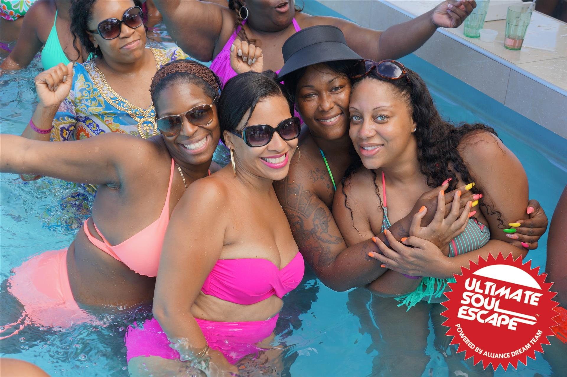 A group of women posing in the pool with their swimwear