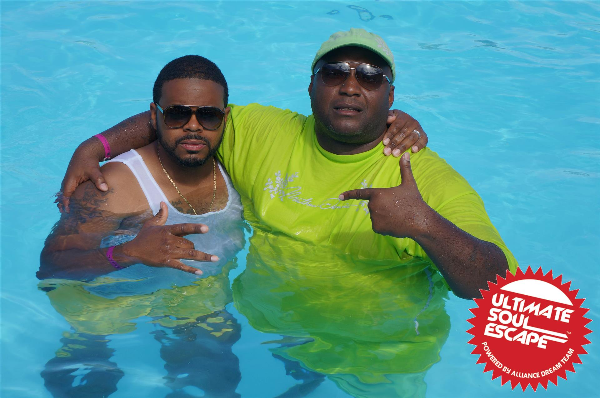 Two guys wearing shirts in a pool