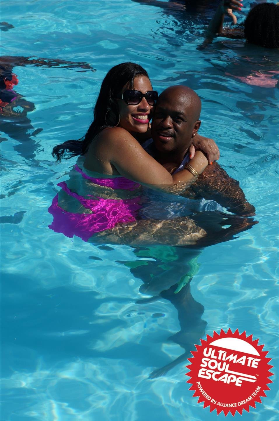 A men holding a girl up in the pool