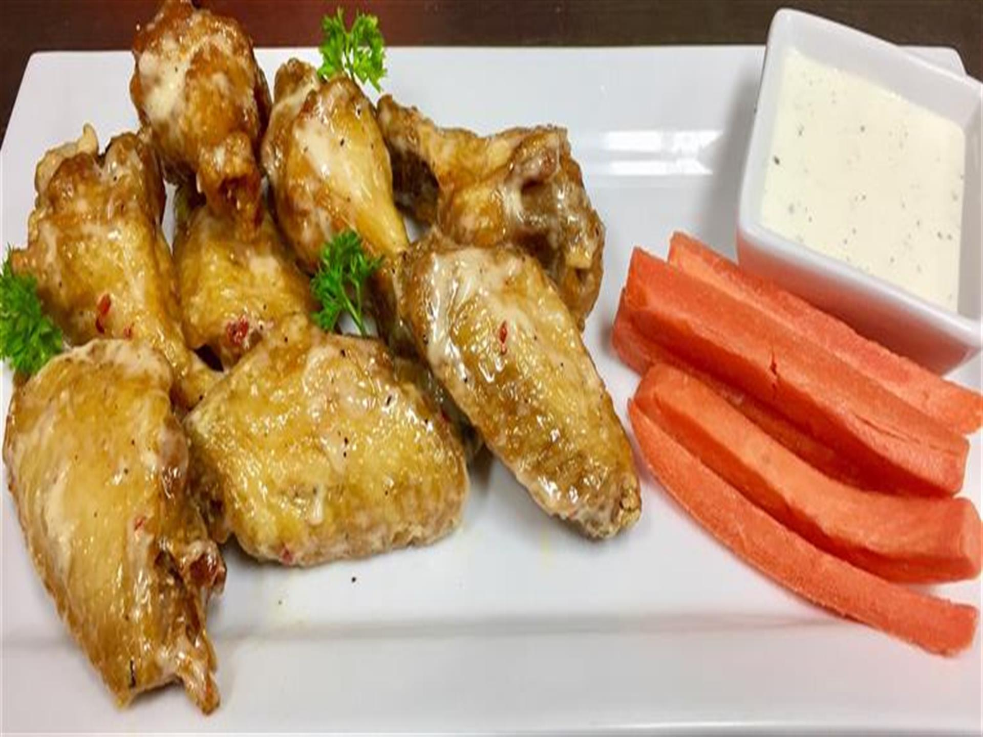 wings with carrots and dipping sauce on a plate