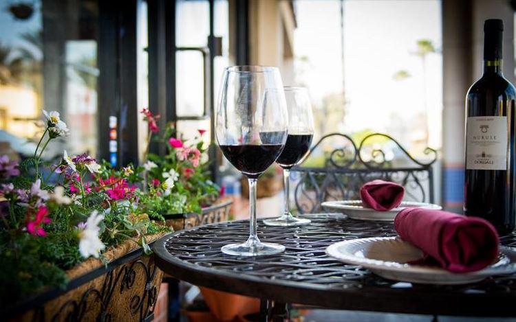 two wine glasses with red wine on a table outside