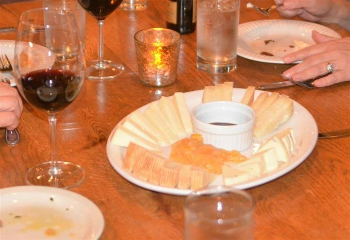 a plate of mixed cheeses and two glasses of wine