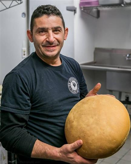 chef holding a big loaf of baked bread