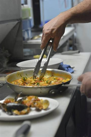 a chef with tongs cooking in a pan