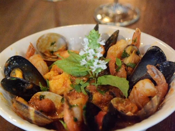 a plate of shrimp and mussels with a garnish