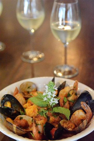 a plate of shrimp and mussels with two glasses of white wine in the background