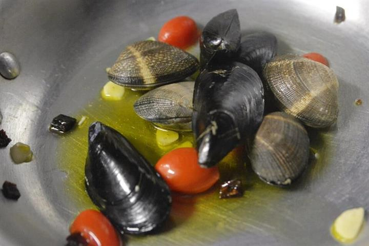 mussels and clams on a pan with tomatoes