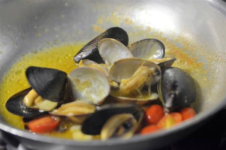 clams and mussels cooking in a pan