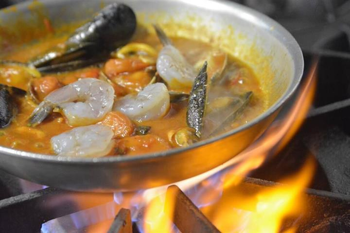 shrimp, mussels and pasta cooking in a pan