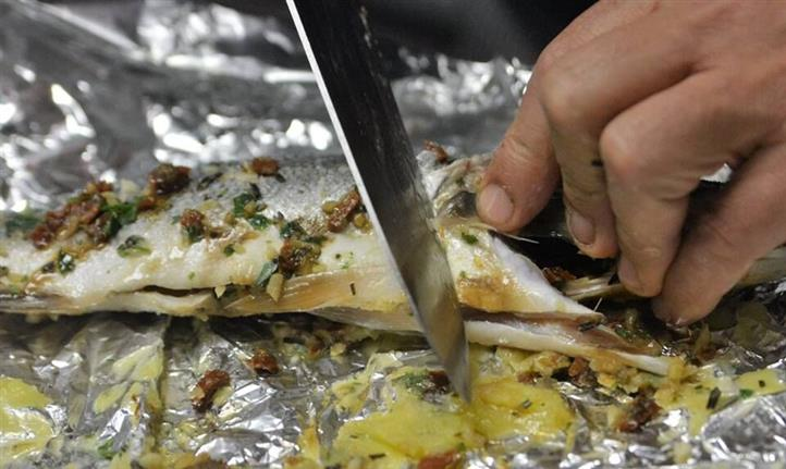 chef cooking the fish in the tin foil with spices