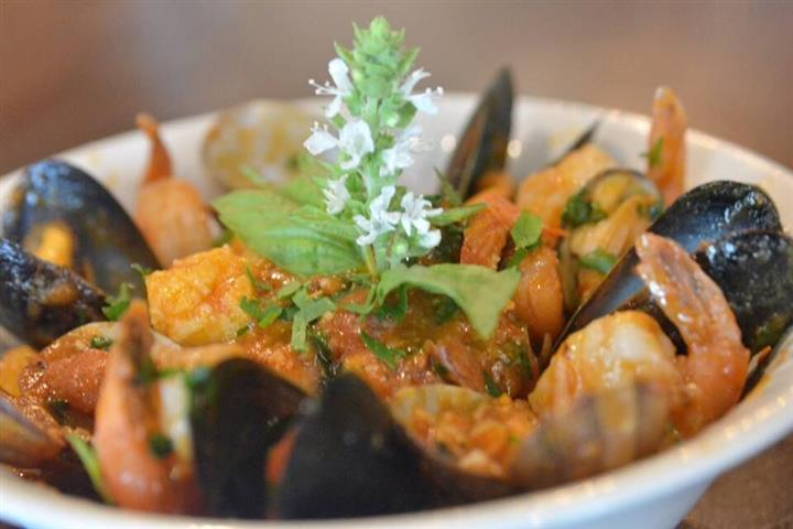 a bowl of mussels and shrimp with a garnish