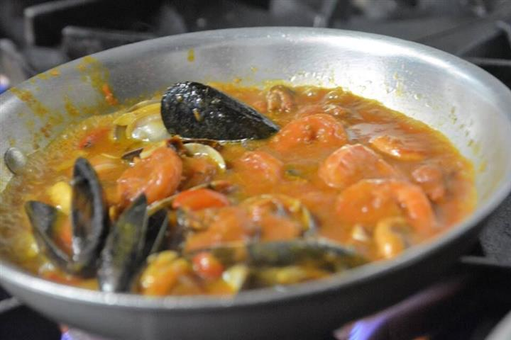 a bowl of stew with shrimp and mussels