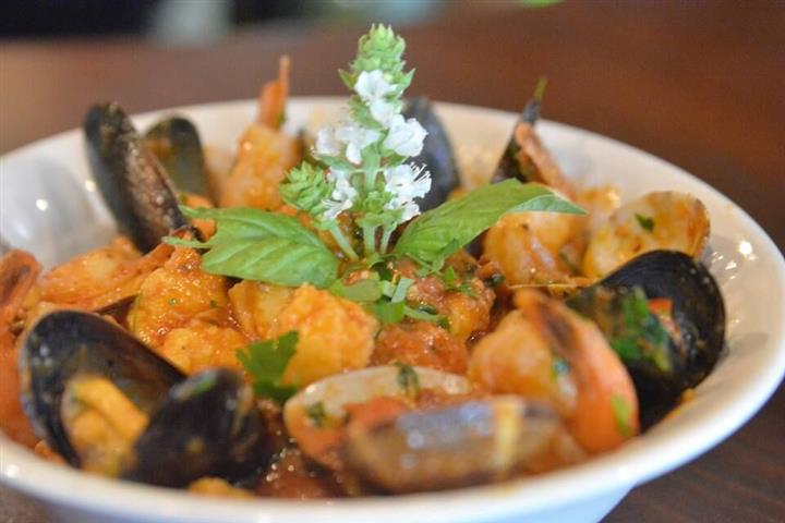 a bowl of shrimp and mussels with a garnish