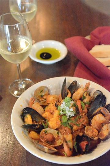 a plate of mussels and shrimp with a glass of white wine