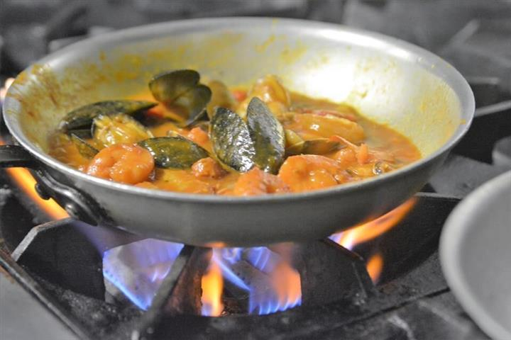 shrimp and mussels in a pan over a stove