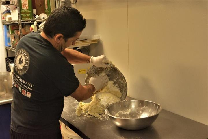 the chef pouring the uncooked dough from the mixing bowl