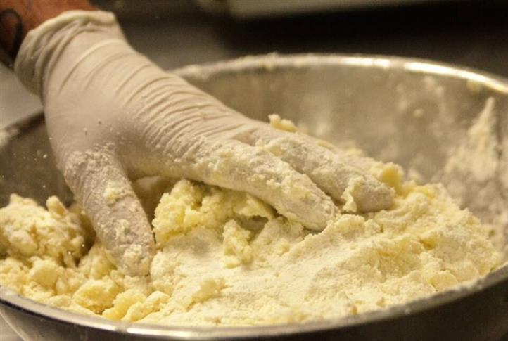 chef putting flour on uncooked pasta