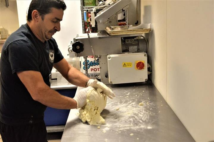 chef kneeding dough to create pasta