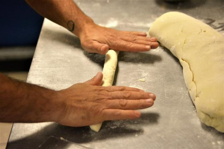 chef rolling up dough to be created into pasta