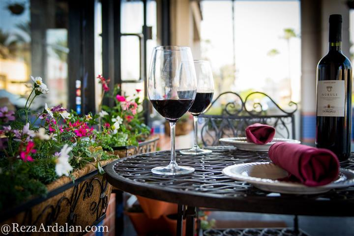a table outside with two glasses of red wine