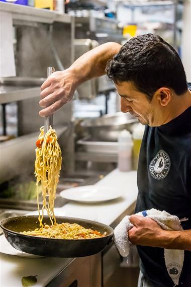 chef making pasta in a pan