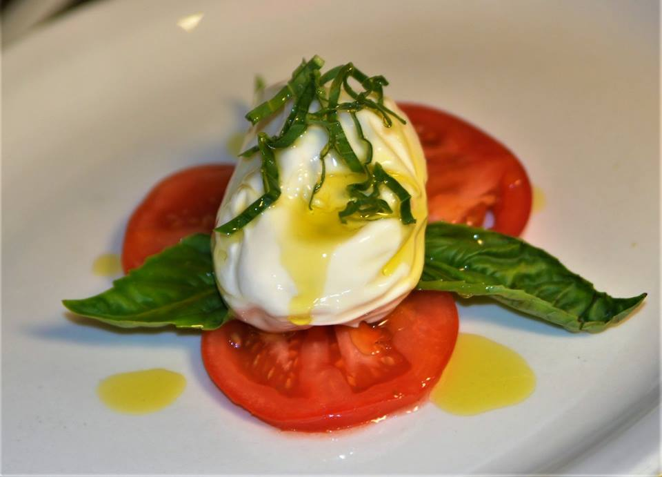 a ball of mozzarella with tomato and basil