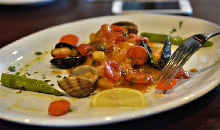 a plate of clams, shrimp, and mussels with tomato and a lemon wedge
