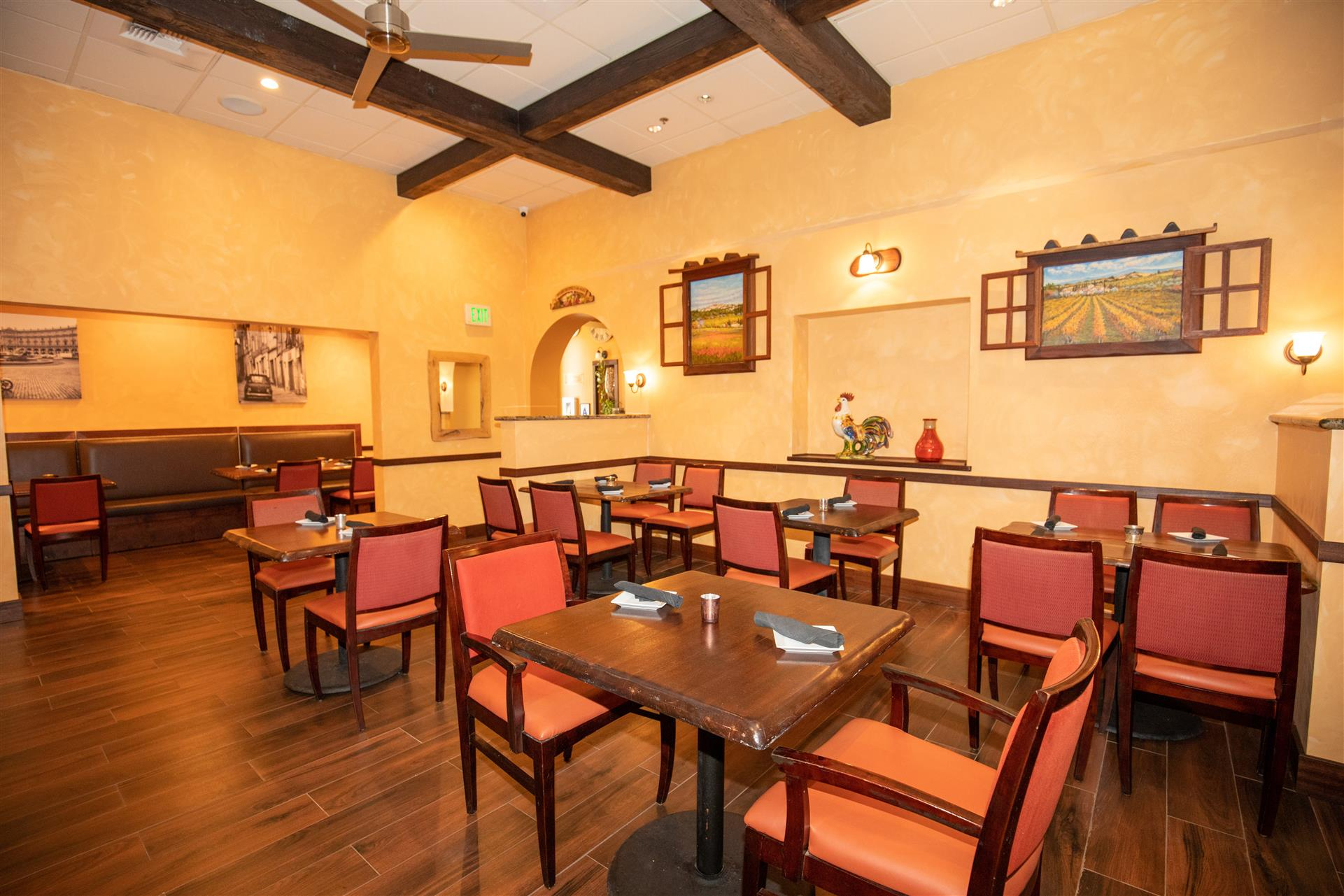 Dining area inside of Trattoria Toscana Italian Restaurant with tables and chairs.