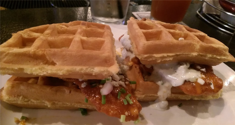 Buffalo chicken and waffles sandwiches with bleu cheese crumble and ranch dressing.