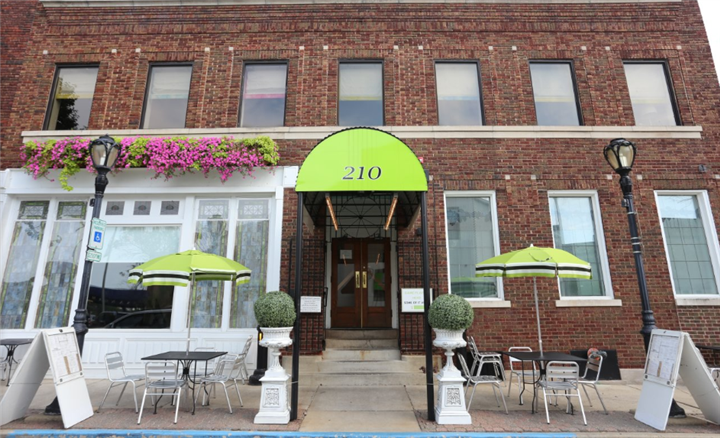 outside Arlington's with table and awning with the number 210 on it