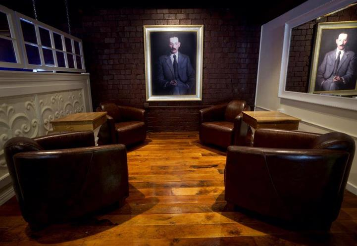 Lounge room with wood floor and lounge chairs. Brick wall with painting of man in suit and tie.