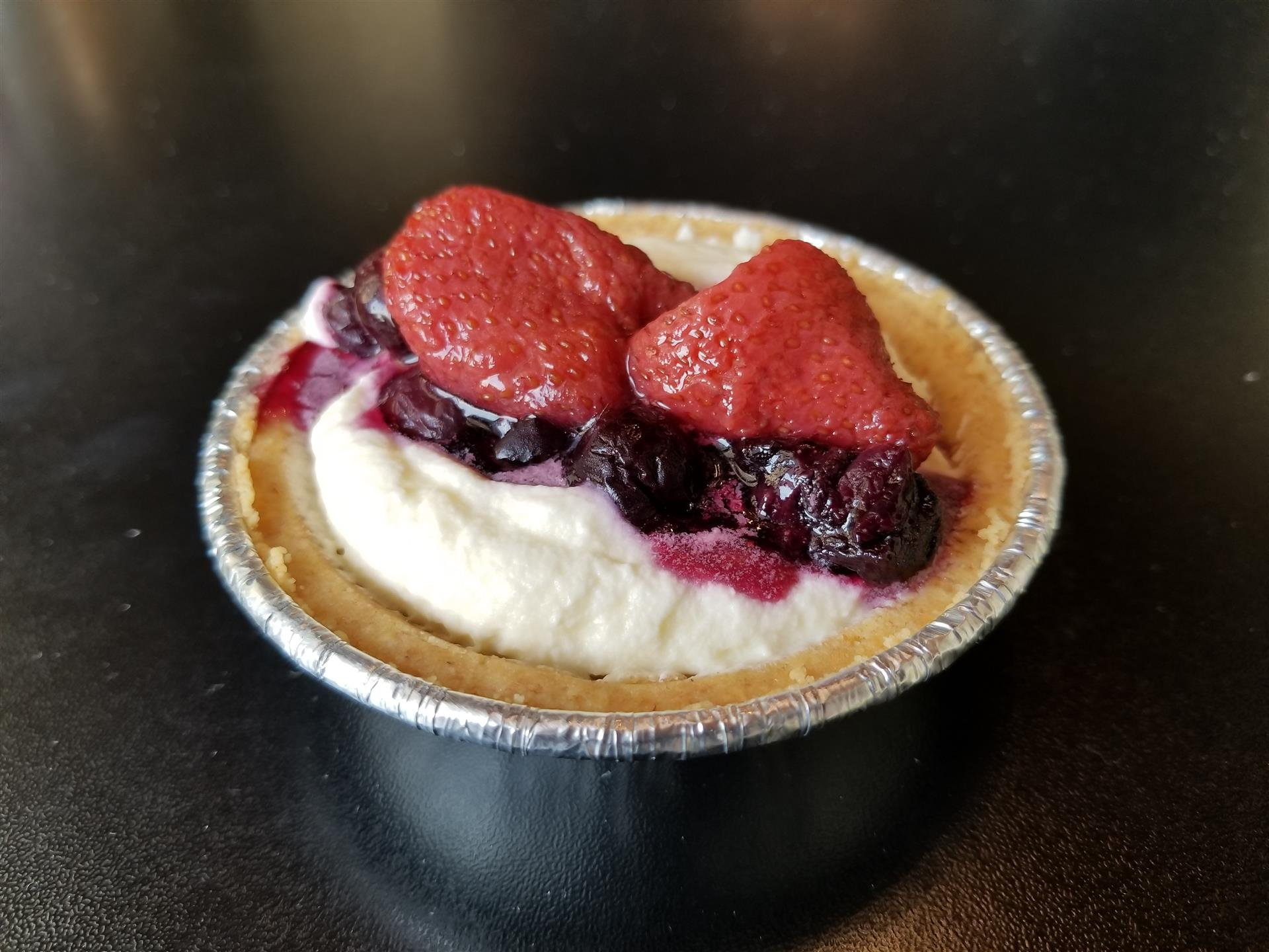 small dessert pie topped with blueberries and strawberries