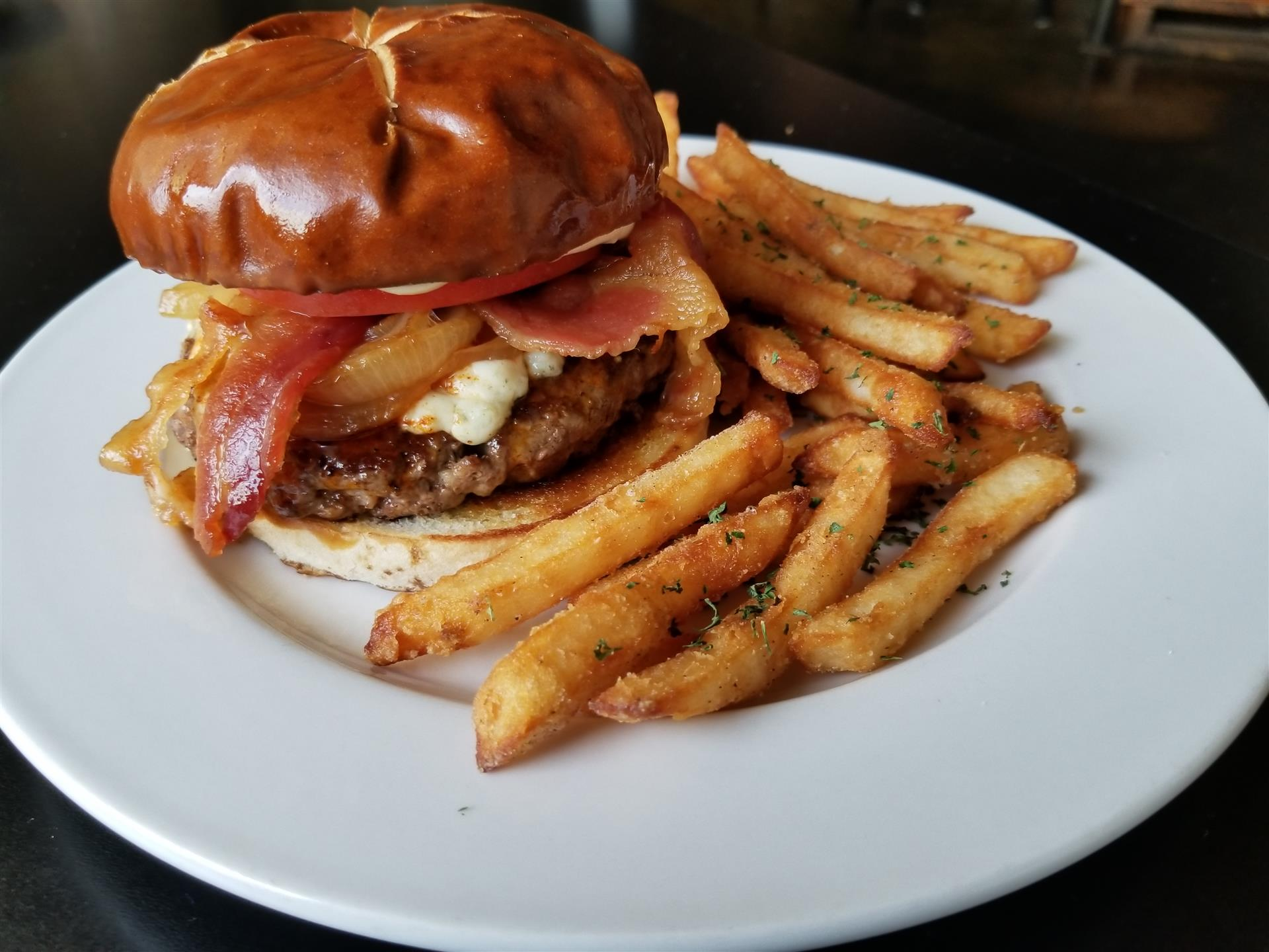 cheeseburger with bacon and tomato with a side of french fries