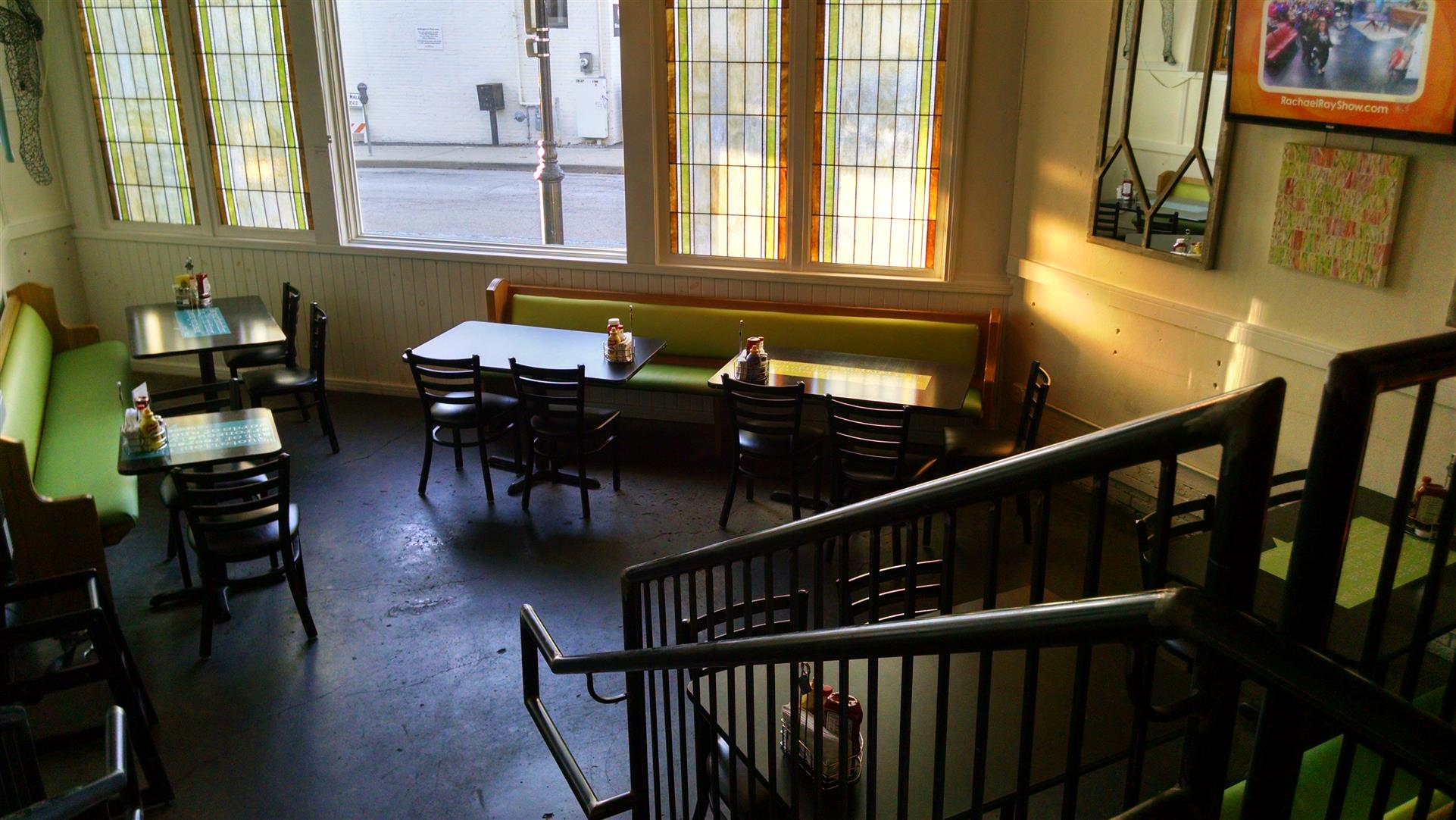inside Arlington's Restaurant looking down steps at seating area with tables and chairs