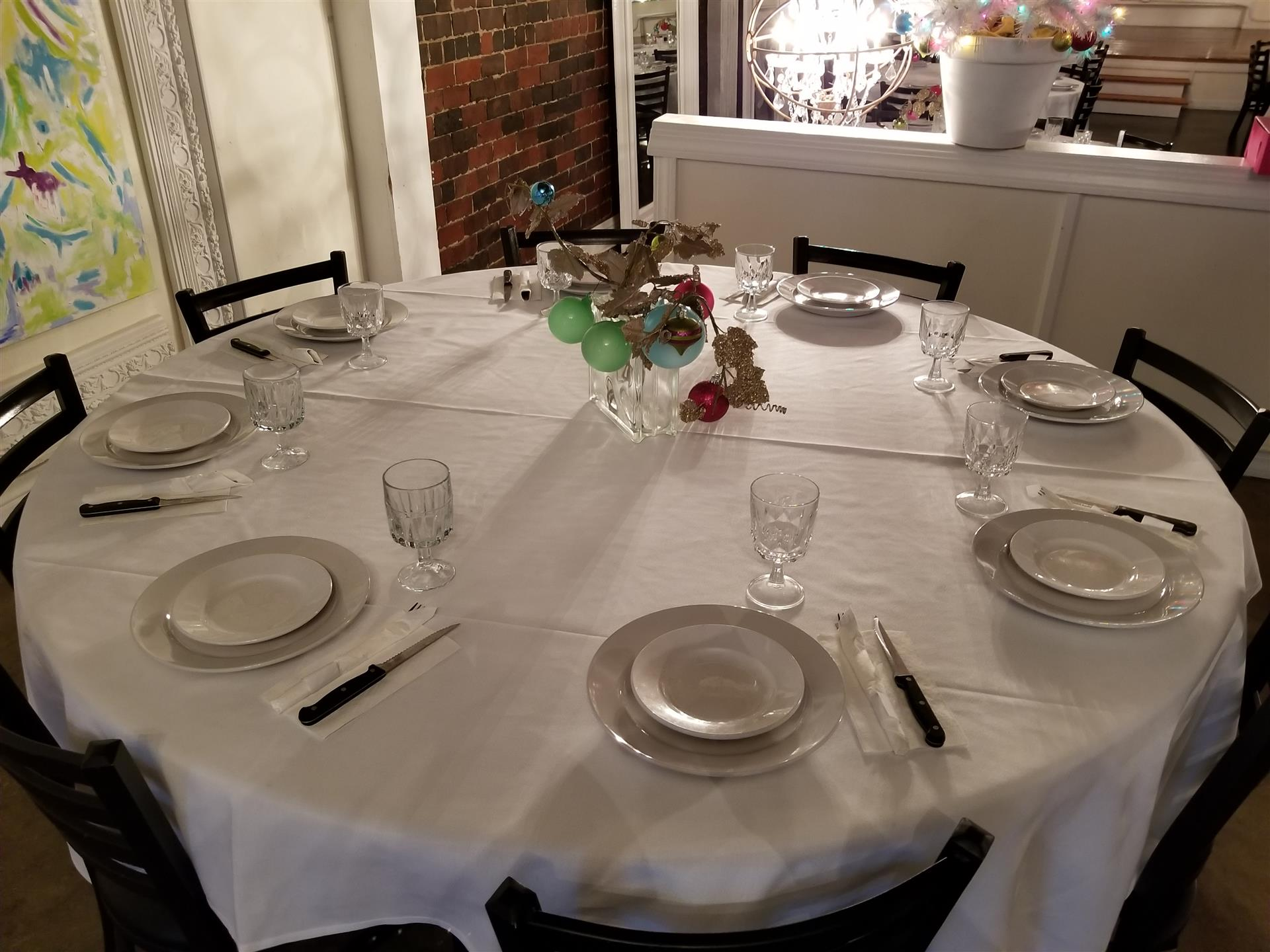 overheard view of round table with plates and silverware