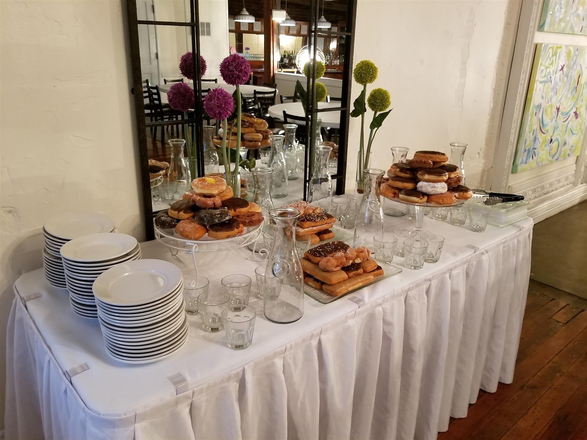 table set up with plates to pick-up donuts and other desserts