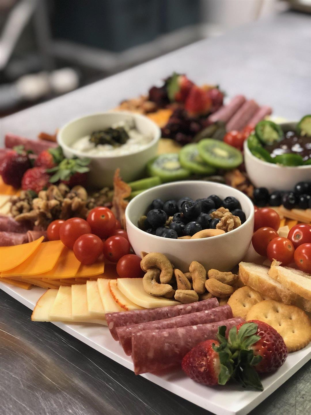 tray with various nuts, fruit, and deli meat
