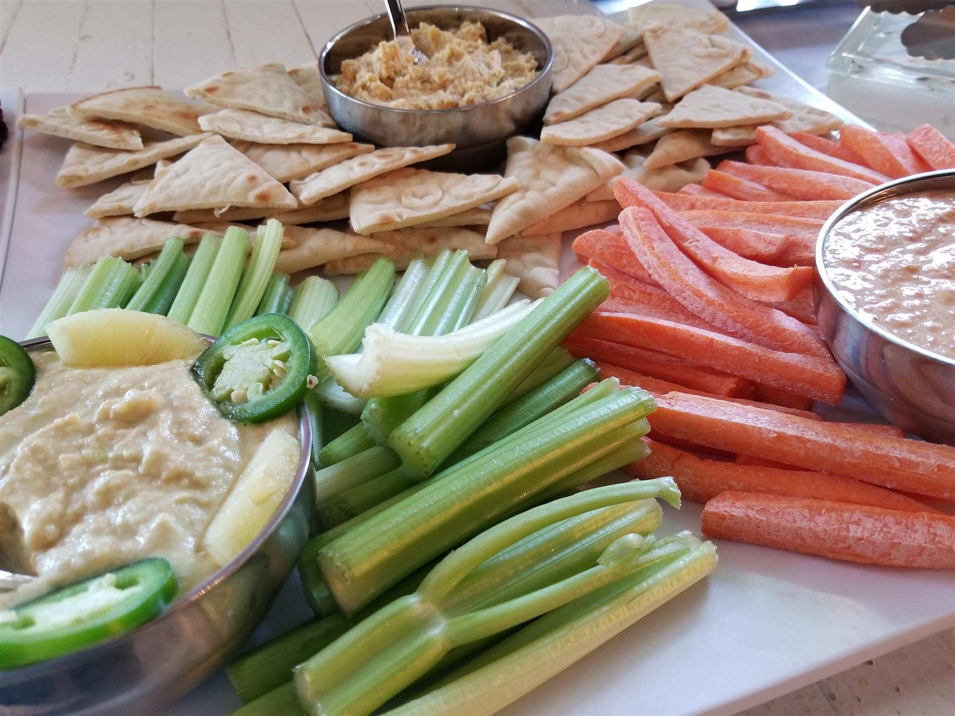 tray with celery and carrots and dipping sauce, with crackers and dipping sauce