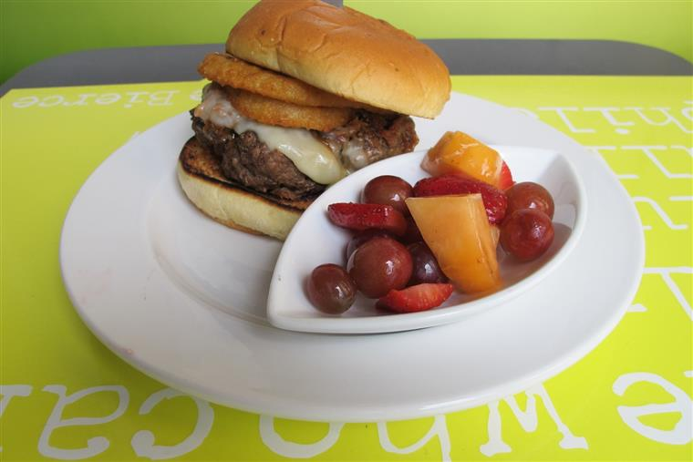Thick hamburger with cheese and onion rings on bun with side of fruit salad on white dish.
