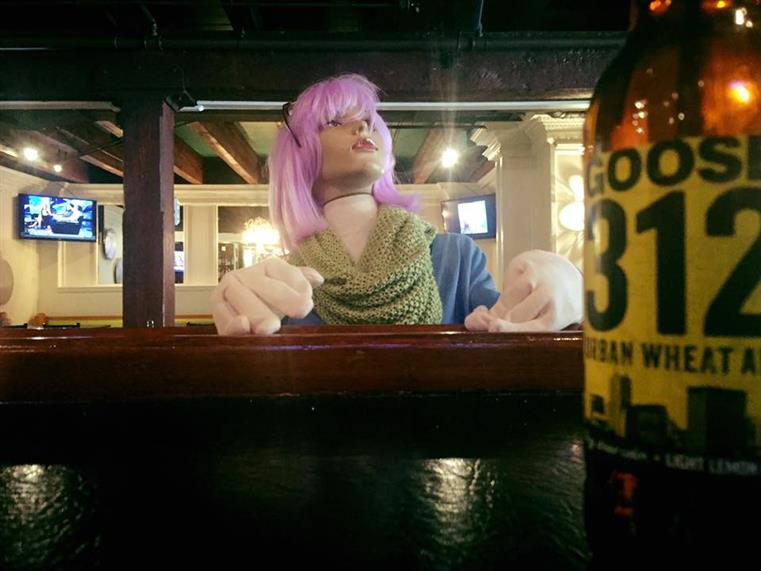Manequin with purple hair, scarf, and gloves at bar with bottle of beer.