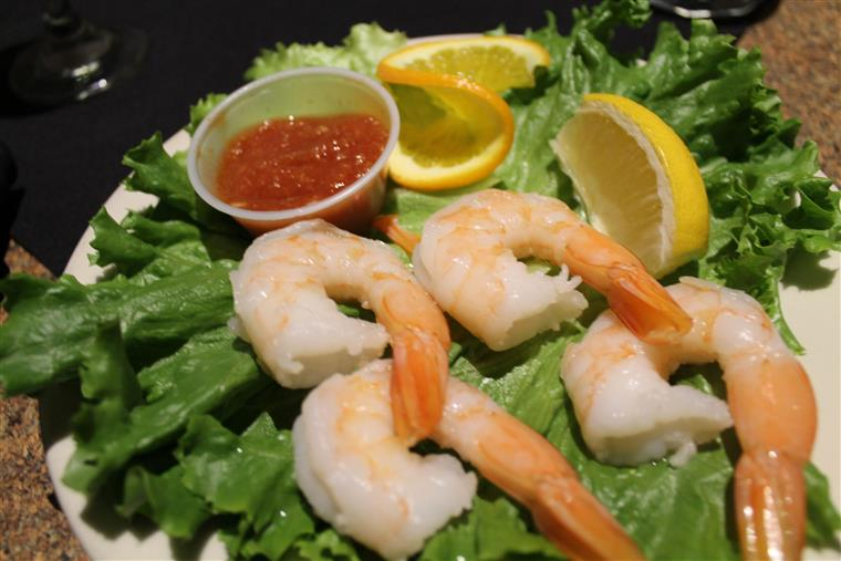 Shrimp cocktail with lemon on bed of lettuce.
