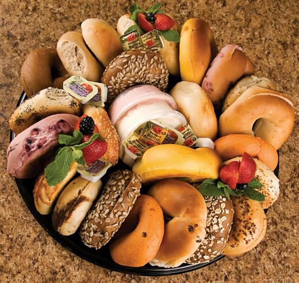 Assortment of bagels on tray on marble counter.