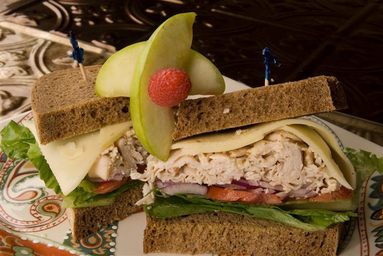 Turkey sandwich with tomato, onions, lettuce on rye bread. Topped with berry and apple slices.