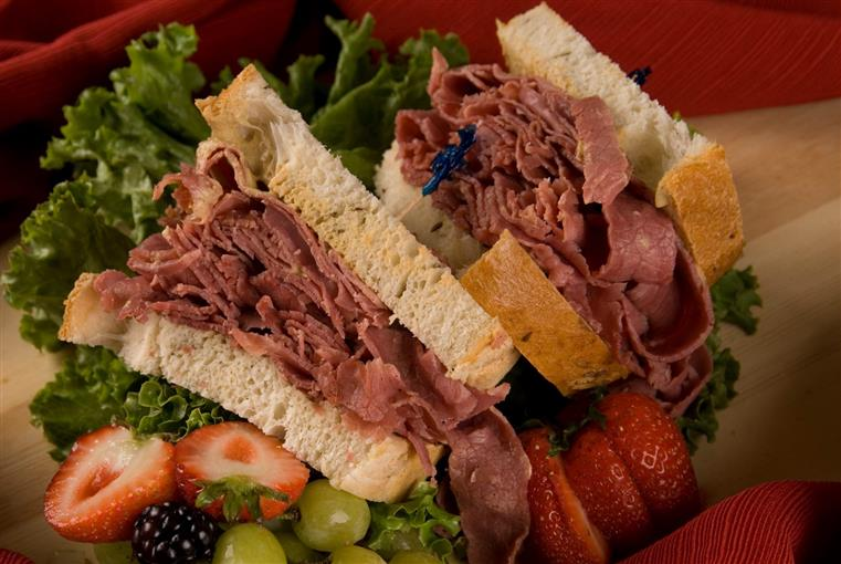 Corned beef sandwiches over fruit and bed of lettuce.