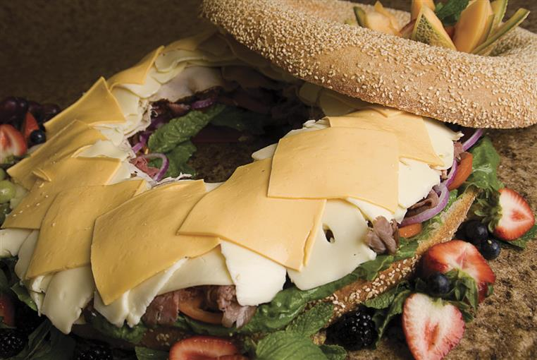 Catering spread - giant bagel sandwich with cheese, lettuce, tomato.