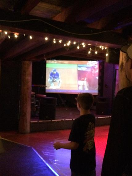 A kid watching football on a tv screen in the restaurant