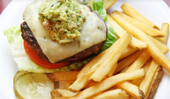 cheeseburger topped with guacamole with lettuce and tomato and french fries on the side